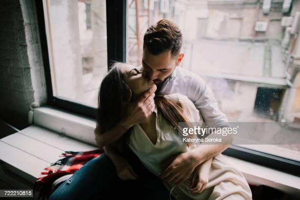 Caucasian couple kissing on window sill