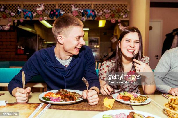 Caucasian couple laughing in restaurant