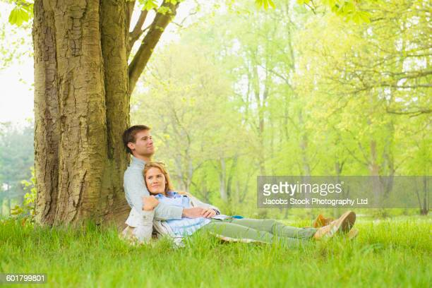 Caucasian couple laying in field