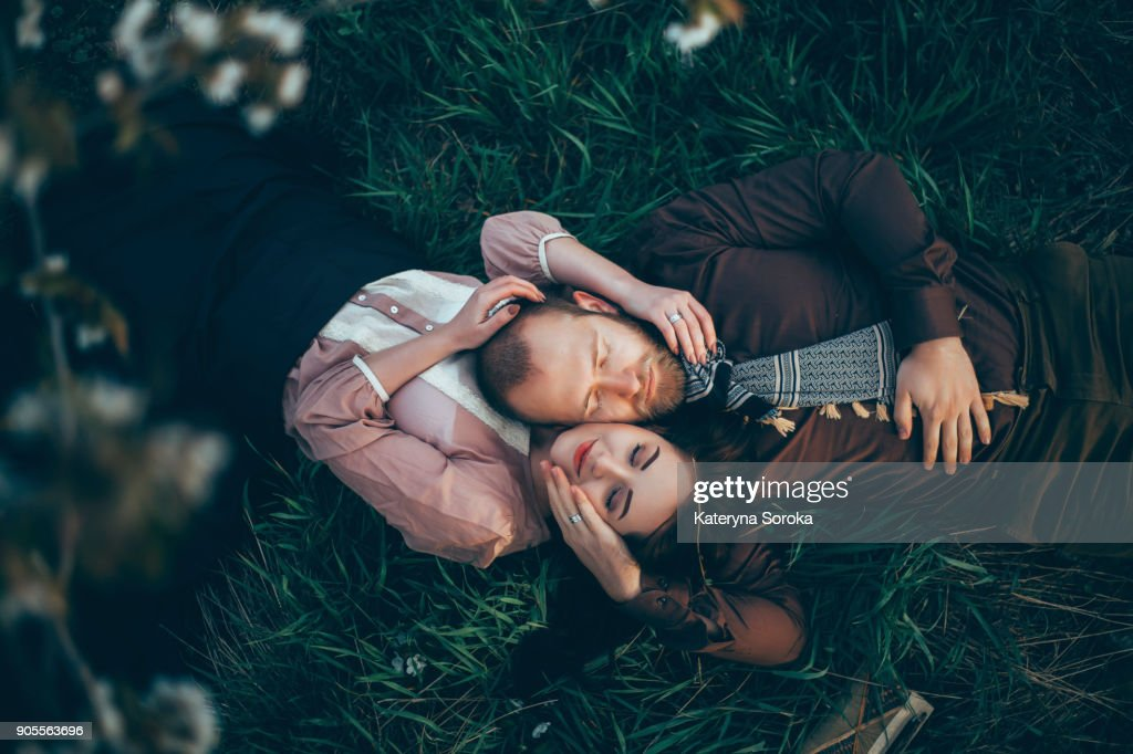 Caucasian couple laying in grass cheek to cheek : Stock Photo