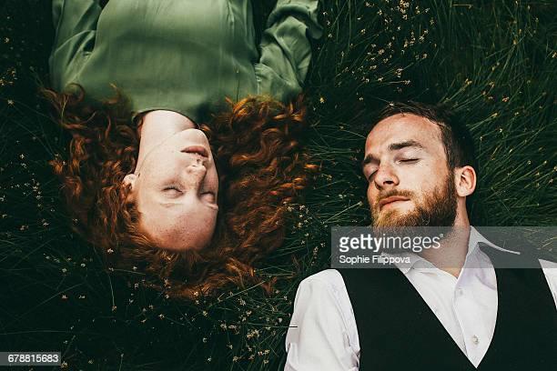 caucasian couple laying in grass - lying down foto e immagini stock