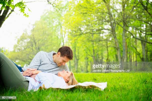 Caucasian couple laying on picnic blanket