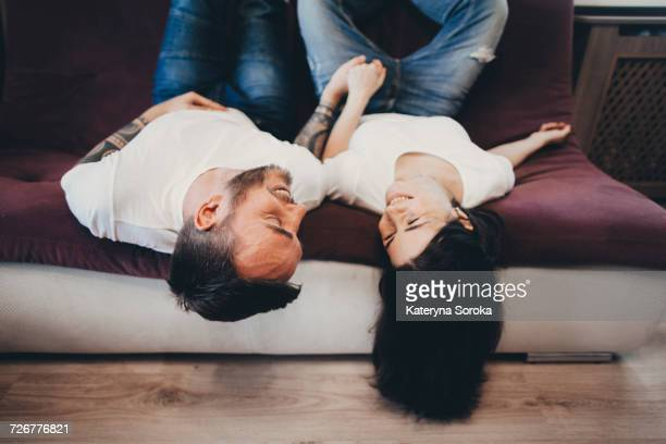 Caucasian couple laying upside-down on sofa