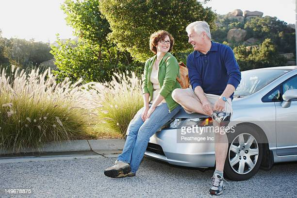 caucasian couple leaning on car - lace fastener stock pictures, royalty-free photos & images