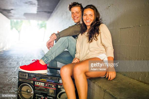 Caucasian couple listening to boom box in tunnel