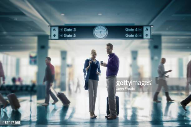 Caucasian couple looking at cell phone in airport