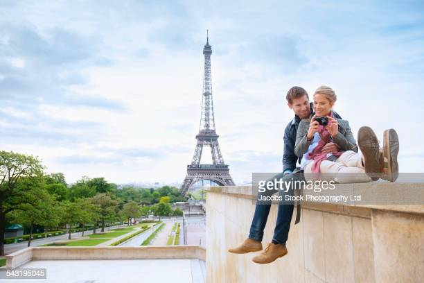 Caucasian couple looking at photographs near Eiffel Tower, Paris, France