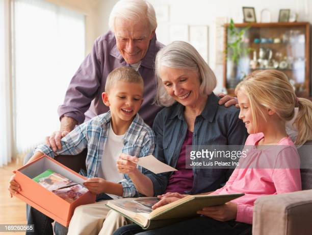 caucasian couple looking at photographs with grandchildren - memorial stock pictures, royalty-free photos & images