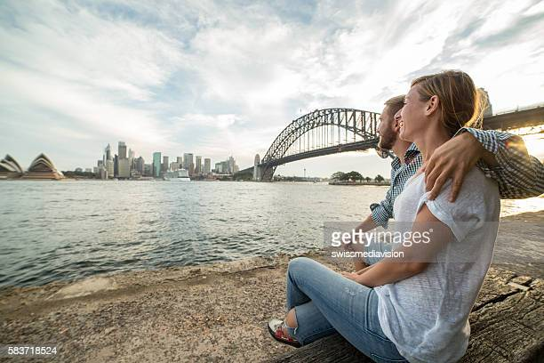 Caucasian couple looking out Sydney skyline at sunset