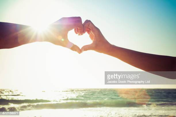 Caucasian couple making heart symbol with hands at beach