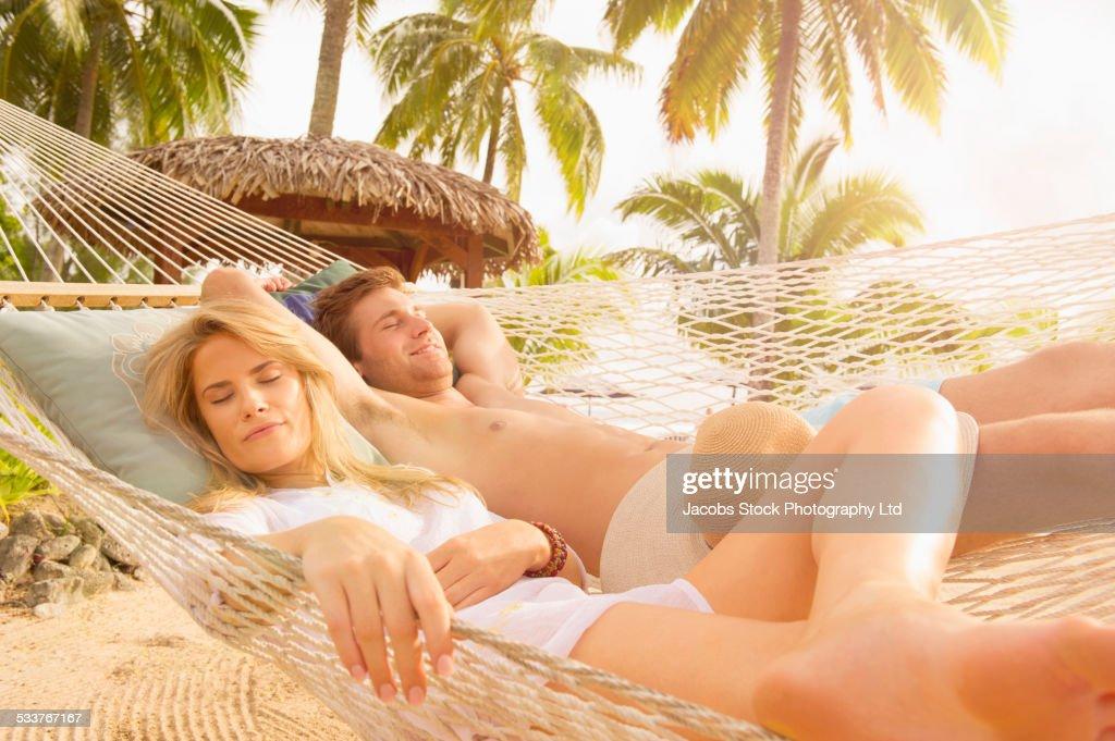 Caucasian couple napping in hammock : Foto stock