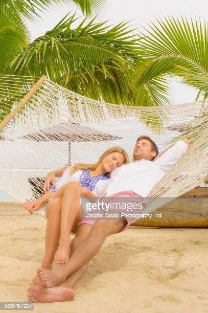caucasian couple napping in hammock - rarotonga foto e immagini stock