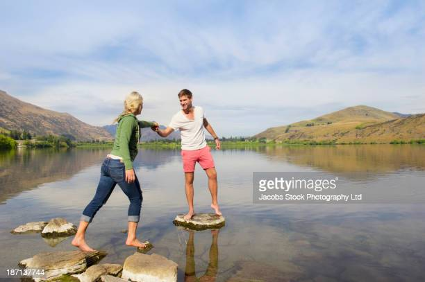 Caucasian couple on stones in rural lake