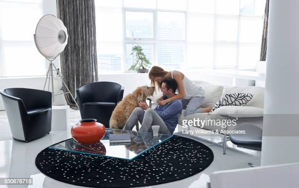 Caucasian couple petting dog in living room