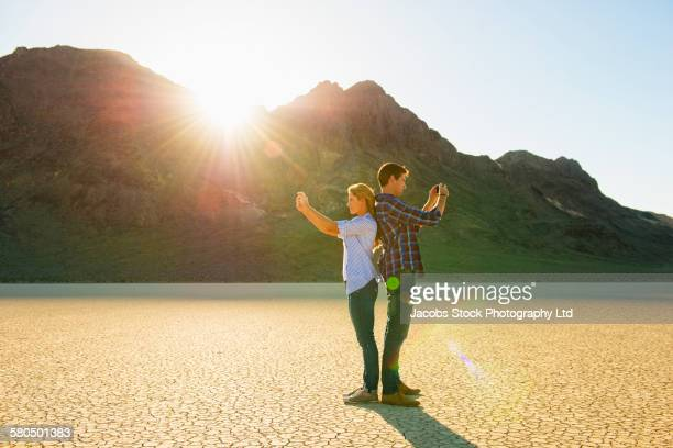 Caucasian couple photographing cracked desert landscape