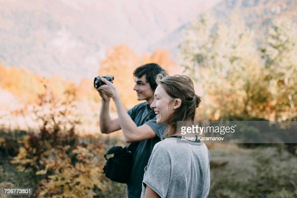 Caucasian couple photographing with camera in autumn