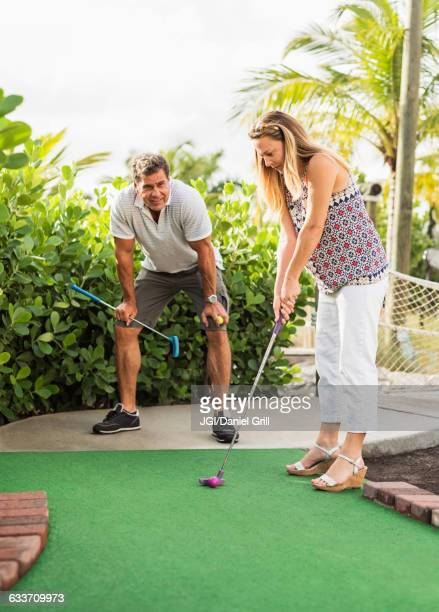 caucasian couple playing miniature golf - miniature golf stock photos and pictures