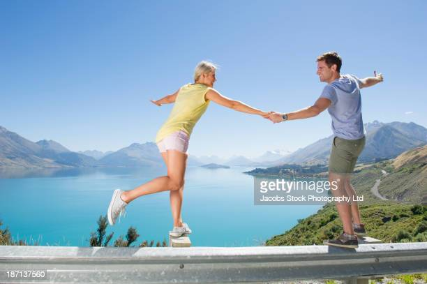 Caucasian couple playing on barrier on rural road