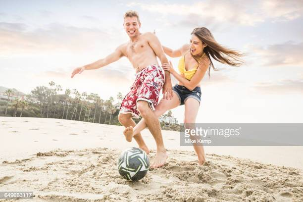 Caucasian couple playing on beach