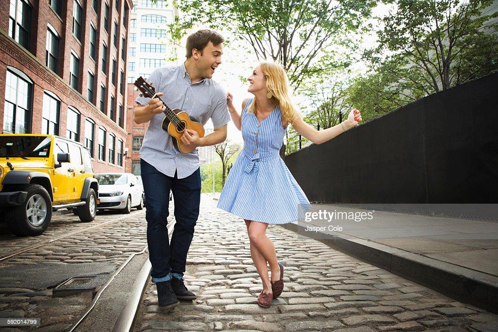 Caucasian couple playing ukulele on city street : Stock Photo