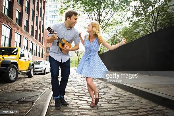 Caucasian couple playing ukulele on city street
