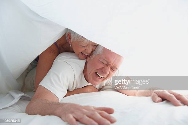 Caucasian couple playing under sheet in bed
