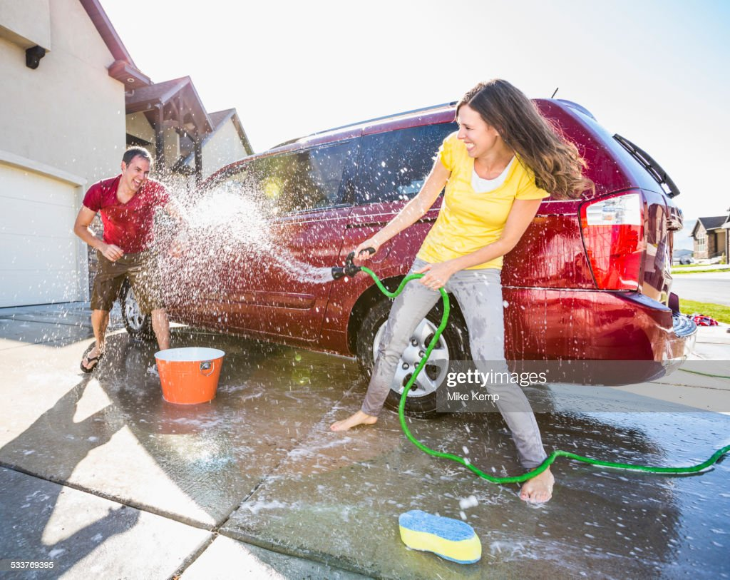 Caucasian couple playing while washing car in driveway : Foto stock