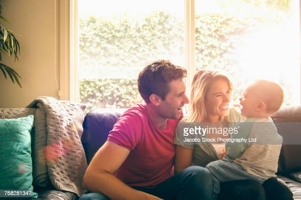 caucasian couple playing with baby son on sofa - junge familie stock-fotos und bilder