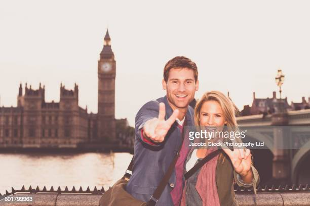 Caucasian couple posing at clock tower, London, Middlesex, United Kingdom