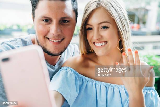 Caucasian couple posing for cell phone selfie showing engagement ring