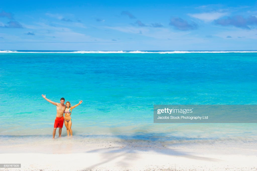 Caucasian couple posing on beach : Foto stock