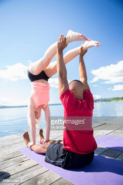 Caucasian couple practicing acroyoga on wooden dock
