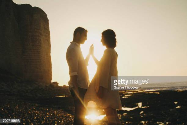 Caucasian couple pressing hands on beach at sunset