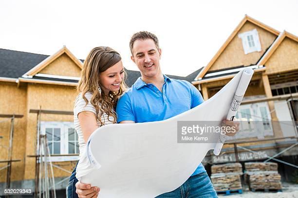 Caucasian couple reading blueprints outside house under construction