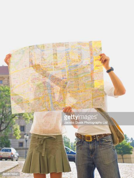 Caucasian couple reading city map outdoors