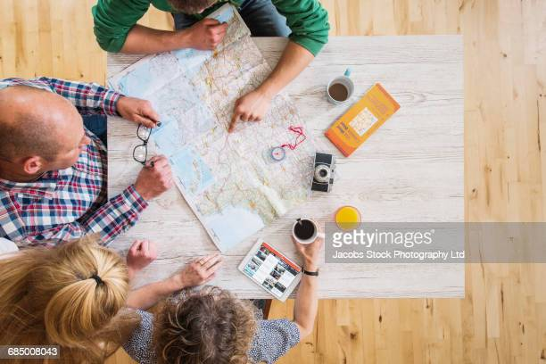 Caucasian couple reading map at table