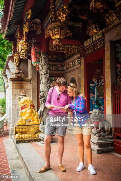 Caucasian couple reading map at Tan Si Chong Su temple, Singapore