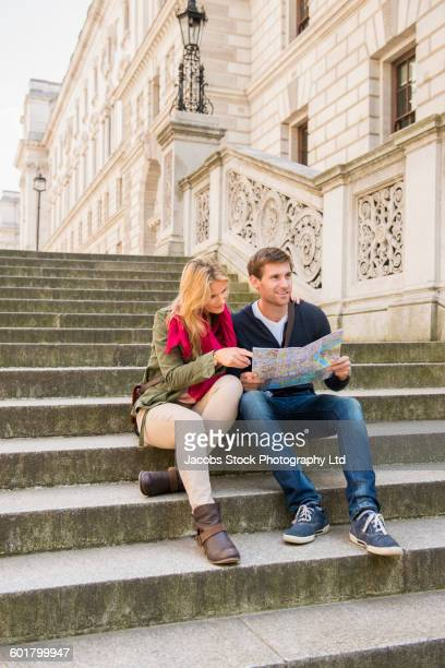 Caucasian couple reading map on steps
