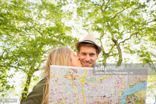Caucasian couple reading map outdoors