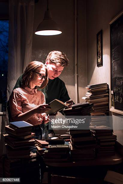 Caucasian couple reading stack of books