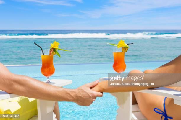 Caucasian couple relaxing in adirondack chairs near swimming pool