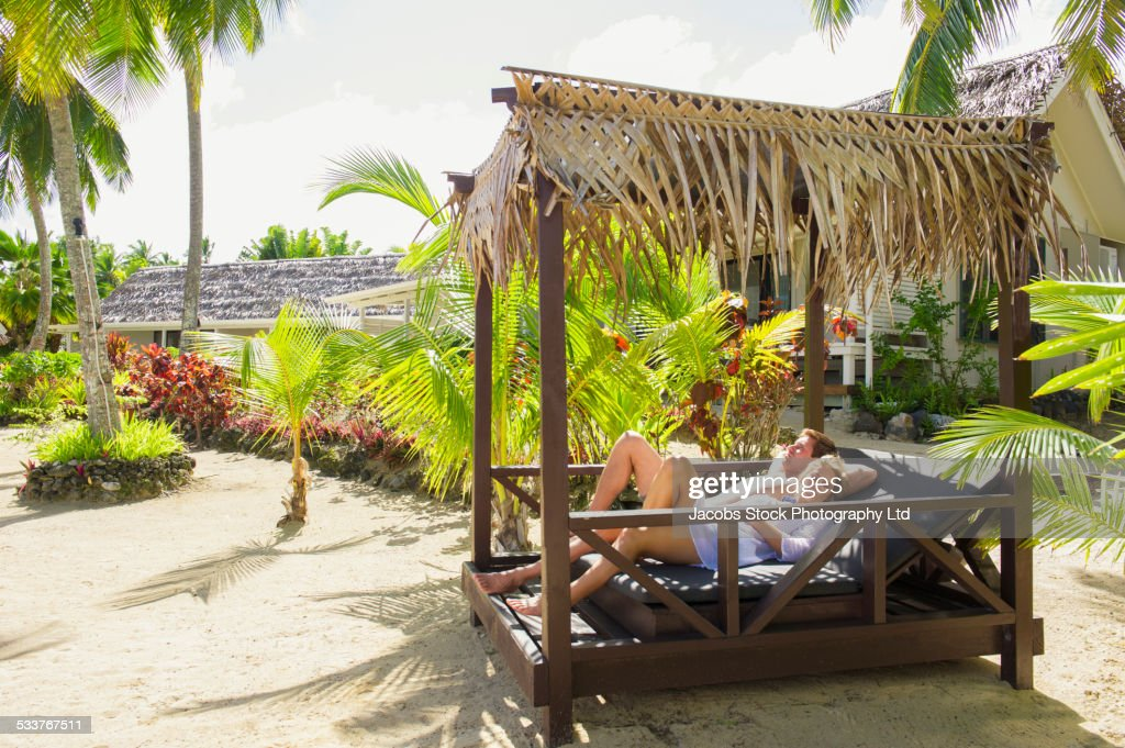 Caucasian couple relaxing in cabana on tropical beach : Foto stock