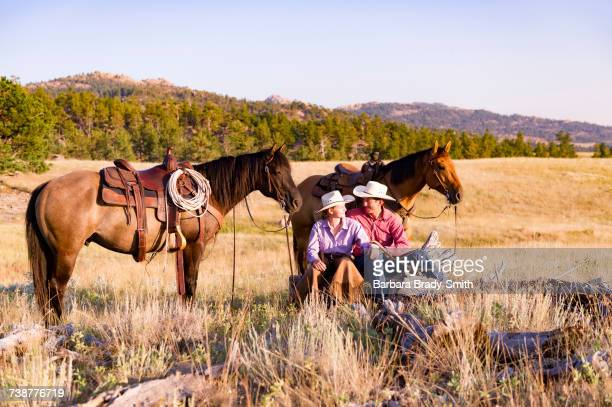 Caucasian couple relaxing in field with horses
