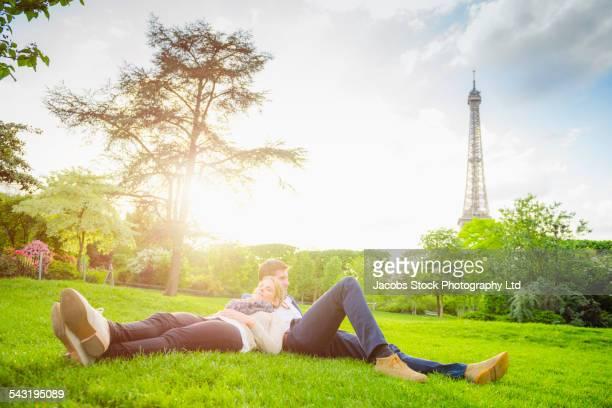 Caucasian couple relaxing in park near Eiffel Tower, Paris, France