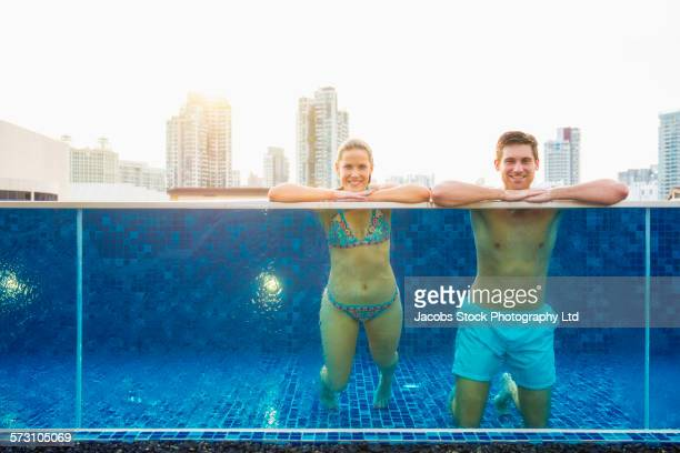 Caucasian couple relaxing in urban rooftop swimming pool, Singapore