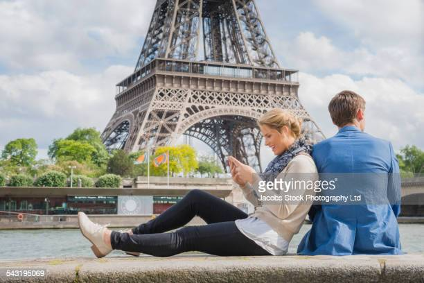 Caucasian couple relaxing near Eiffel Tower, Paris, France