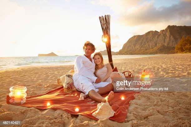 Caucasian couple relaxing on beach blanket
