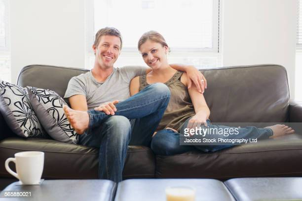 caucasian couple relaxing on living room sofa - wife stock pictures, royalty-free photos & images