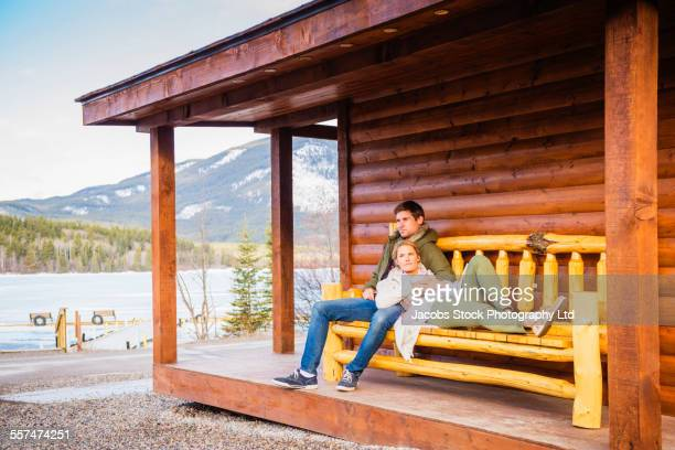Caucasian couple relaxing on log cabin porch