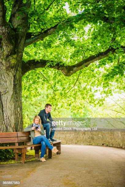Caucasian couple relaxing on park bench